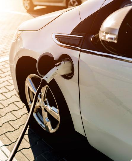 Nowoczesny biały samochód podłączony do stacji ładowania samochodów elektrycznych